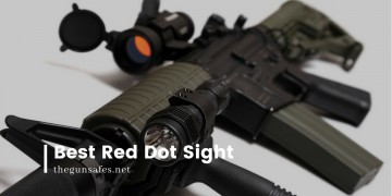 Red dot sight on top of a gun laying down with a torch on it