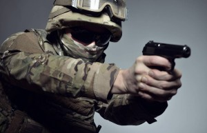 Military man in camouflage uniform, armor vest, dark glasses and helmet with gun aiming