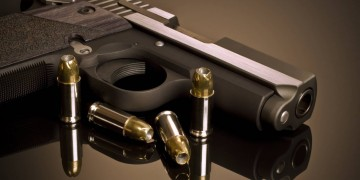 gun a glass background with bullets
