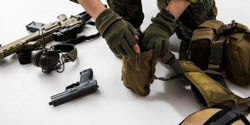 defender hands placing modern army things in a bag