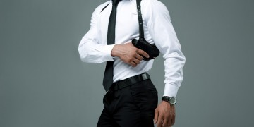 cropped image of a man holding his gun on a shoulder holster