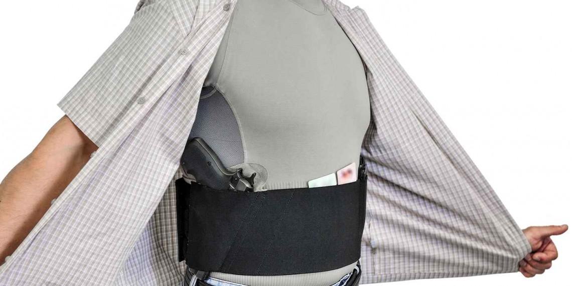 Civilian man hiding his belly band holster with a gun