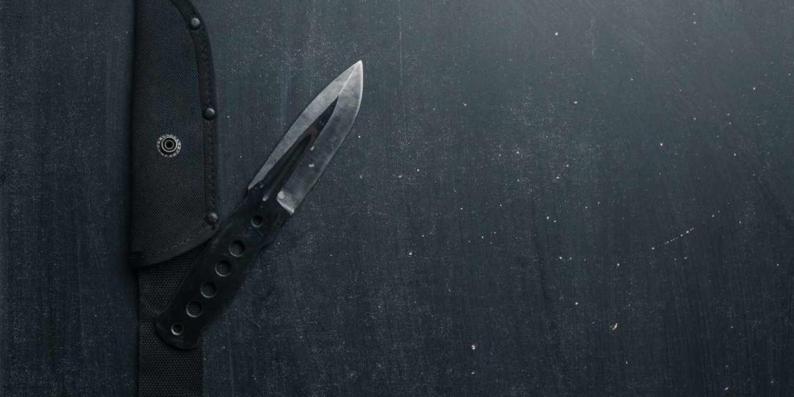 Black tactical knife on black background