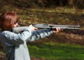 Woman aiming a shotgun