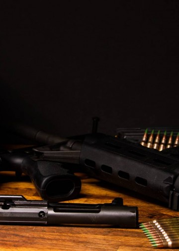 AR-15 broken down in dark setting with ammunition