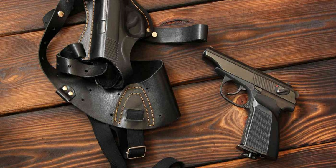 The gun and holster for a handgun on wooden background