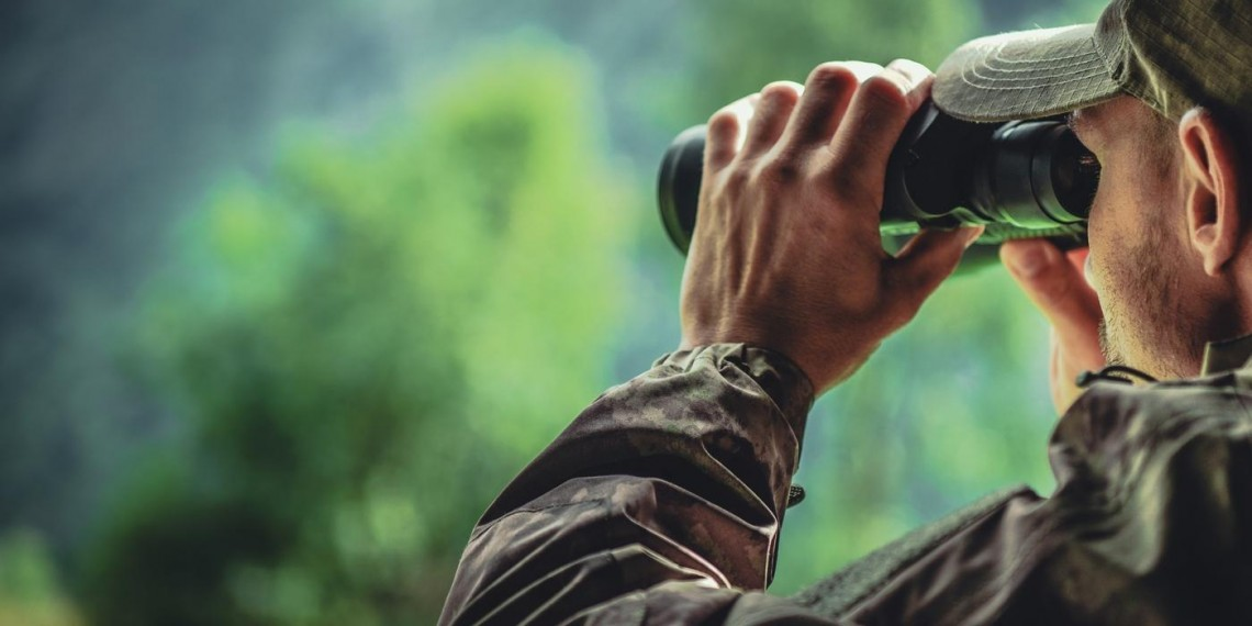 hunter on camouflage attire spotting on binoculars