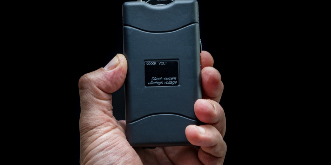 Hand holds a stun gun in front of black background