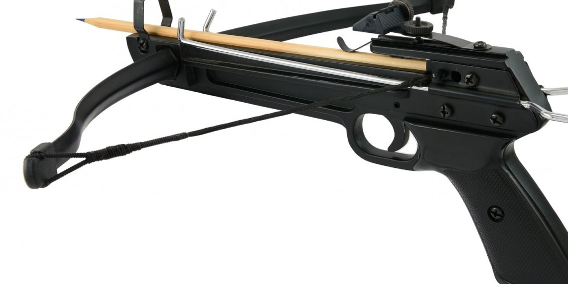 Metal crossbow handgun with wooden pencil isolated on white