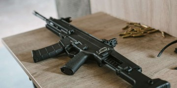 black rifle with bullets on wooden table