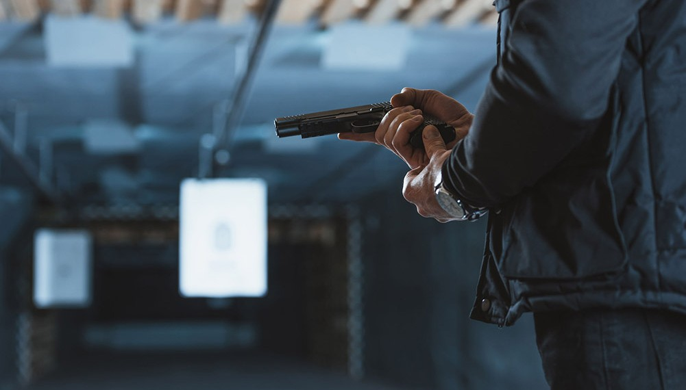 man loading a gun in shooting range