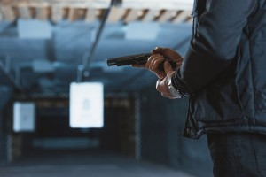 Man loading gun at the shooting range with targets in the background