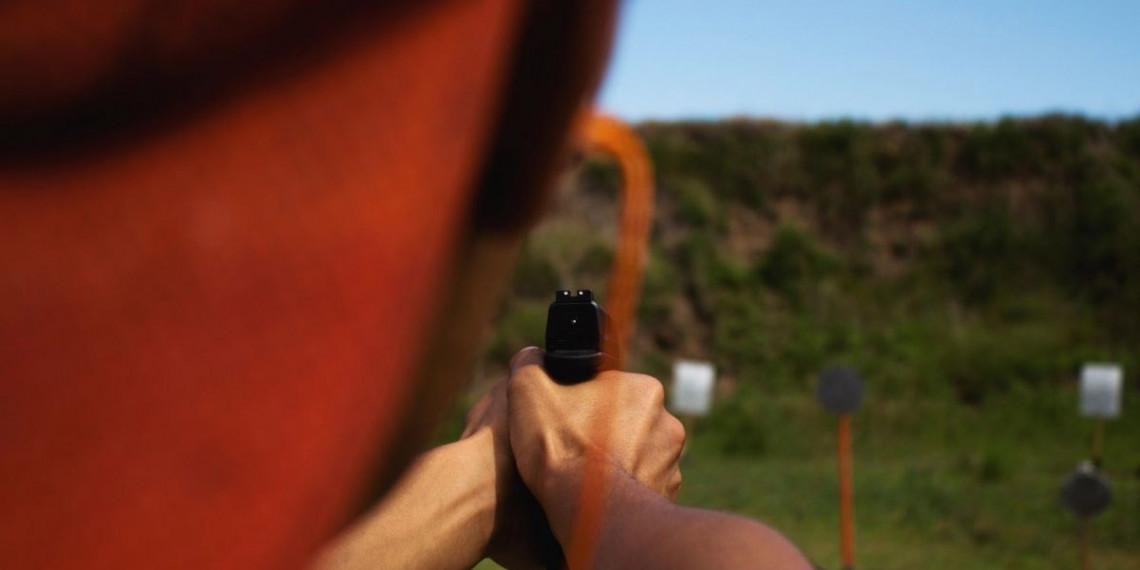 view over a mans shoulder shooting a handgun