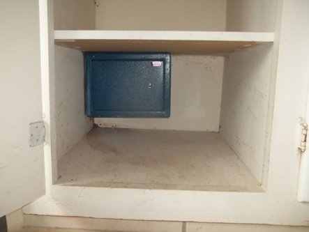 Small gun safe attached to a concrete wall in closet